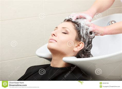 washing hair in in hairdressing salon hairstylist washing hair woman