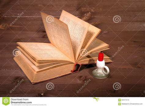small candle table ls the old book and candle on a wooden table stock photo