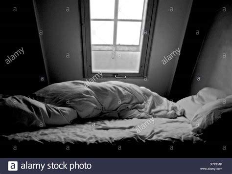 piumone con foto un letto disfatto con piumone in mansardata sotto