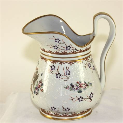 antique white porcelain pitcher with painted crest