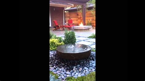 modern backyard stone water feature  concrete fire pit