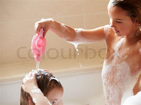 two girls in a bathtub two girls sharing bubble bath and washing hair stock