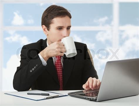 Person Sitting At A Desk by Successful Business Working The Notebook Sitting At A Desk With A Cup Of