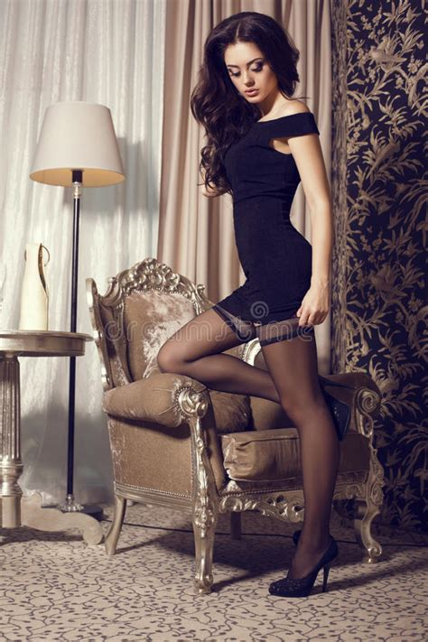 sexy bedroom dress up glamour woman in black dress and pantyhose stock photo