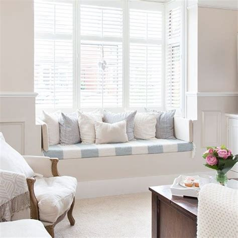 living room with window seat white shutters