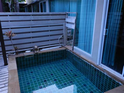 small permanent pool with square shaped pool and beautiful checkered style tiles also wooden