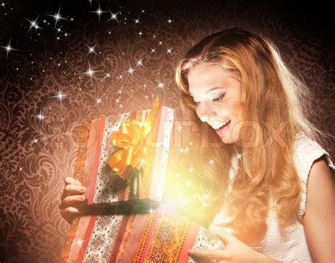 young happy  emotional teenage girl opening  magical christmas present box stock photo