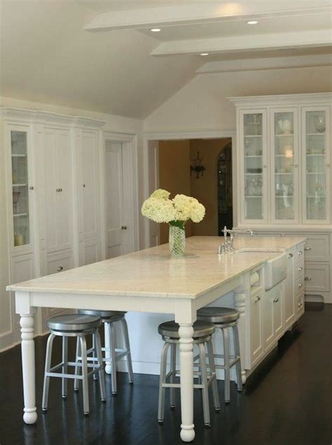 kitchen table integrated  island white cabinets