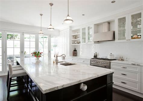 white kitchen with black island calcutta marble countertop transitional kitchen