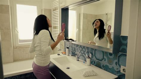 girl dancing in bathroom wide shot female client sitting in hair salon