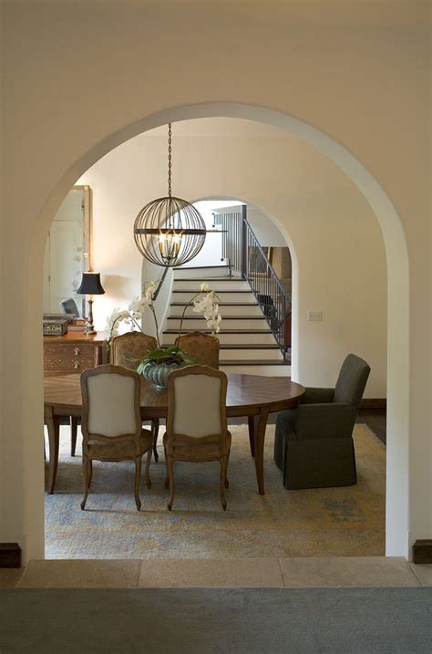 mixing modern chandelier with a traditional oval dining table for style and beautiful room wood with
