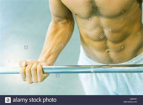 c section lifting man lifting barbell close up of mid section stock photo