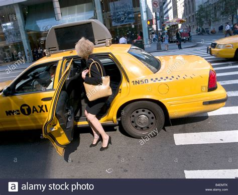 a woman gets a new getting into a yellow cab on fifth avenue in