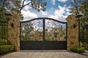 Wrought iron gates landscape mediterranean with brick driveway entry