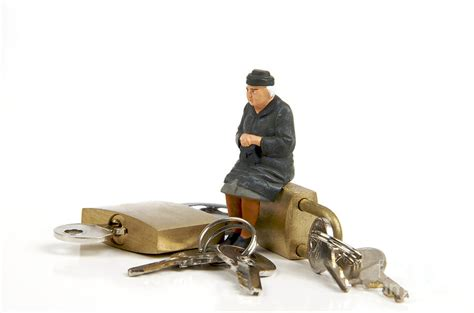 miniature figurines of elderly sitting on padlocks