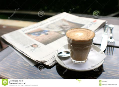 on table cup of coffee with news paper on table royalty free stock