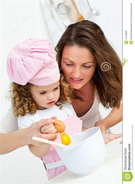 mama e hija cocinando madre e hija que rompen los huevos mientras que cocina