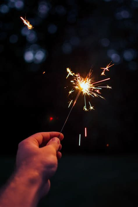 selective focus photography person holding lighted sparkler  nighttime  stock photo