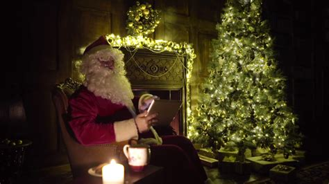 santa claus working shopping gifts on line with tablet