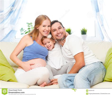 mom on sofa happy family pregnant mother father and child daughter
