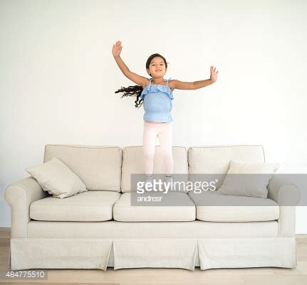 jumping on the sofa happy girl jumping on the sofa stock photo getty images