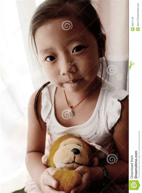 asian child holding  toy monkey stock photo image