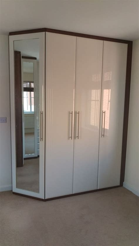 Fitted wardrobe with angled end door and recessed mirror with Dark Walnut carcass and high gloss
