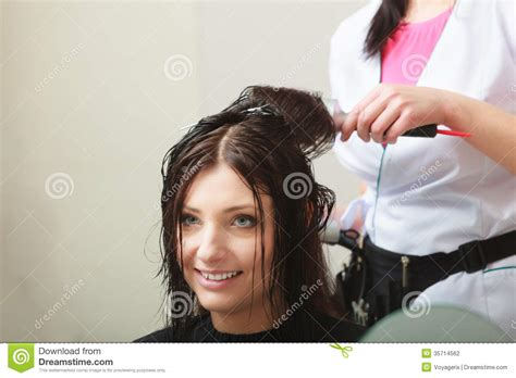 hairstylist drying hair client in hairdressing