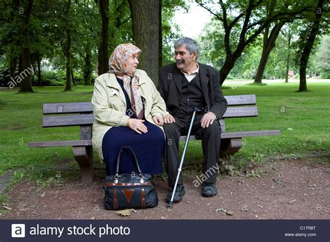 old couple on park bench an elderly turkish couple sitting on a bench in a park