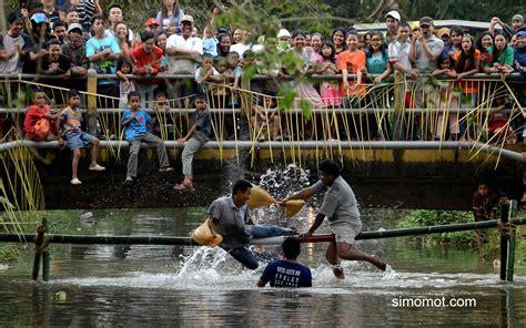 Bantal Makassar dua peserta lomba pukul bantal beradu di atas batang bambu