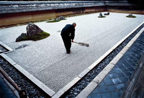 ryoanji rock garden apprentice monk rakes the garden at ryoanji a zen temple