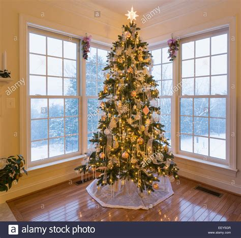 christmas tree in modern home with snow falling outside