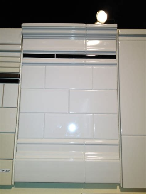 white subway tile with crown molding and baseboard trim