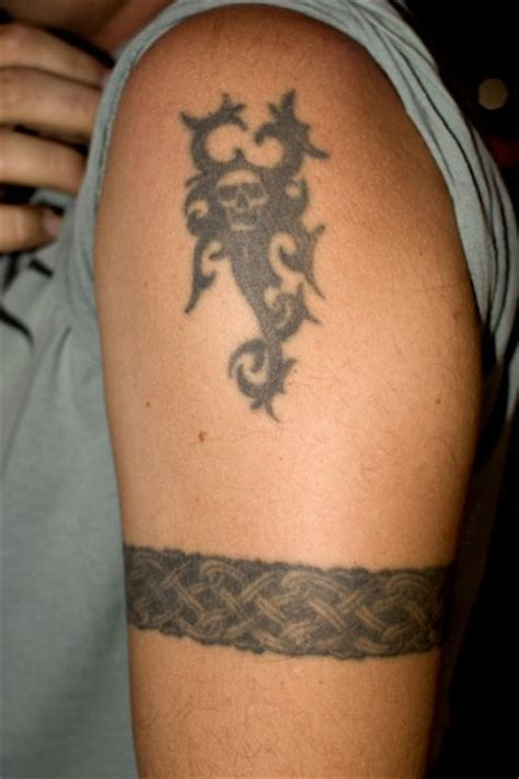 celtic armband and tribal tattoo on left shoulder