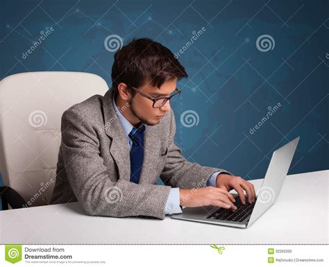 Man Sitting At A Desk Young Man Sitting At Desk And Typing On Laptop Stock Photo