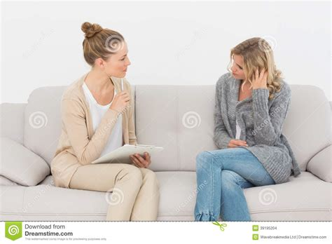 couch counseling upset woman talking to her therapist on the couch stock