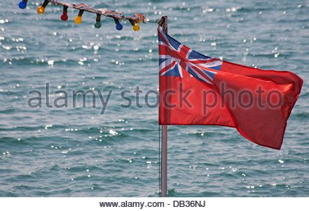 boat flying yellow flag red ensign flag flying on the stern of a civilian boat in