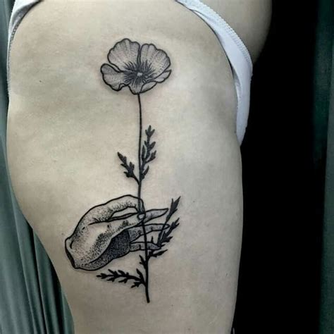 tattoo of a hand holding flowers black ink engraving style thigh tattoo of human hand