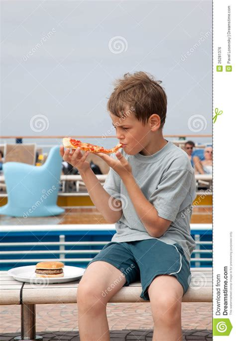 eating bench boy sitting on bench eating pizza royalty free stock image