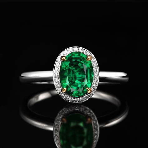 1 carat oval cut emerald and halo engagement ring