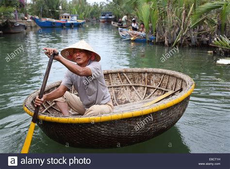 small boat vietnam vietnamese man in non la hat rowing bamboo boat in hoa an