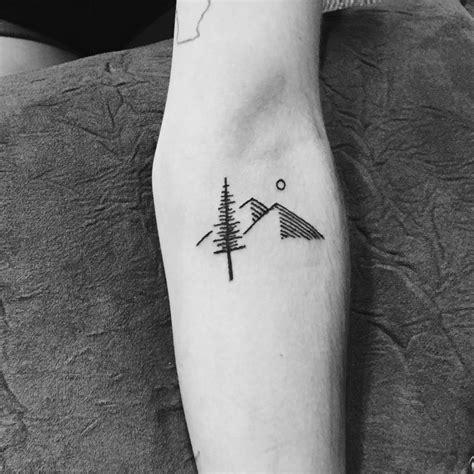 minimalist tattoo artist minneapolis simple black ink tree with heels and moon tattoo on forearm