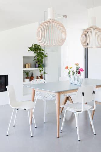 witte woonkamer stoelen grijze eettafel met verschillende witte stoelen
