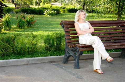 sitting on the bench beautiful sad young woman sitting on the dark bench in the