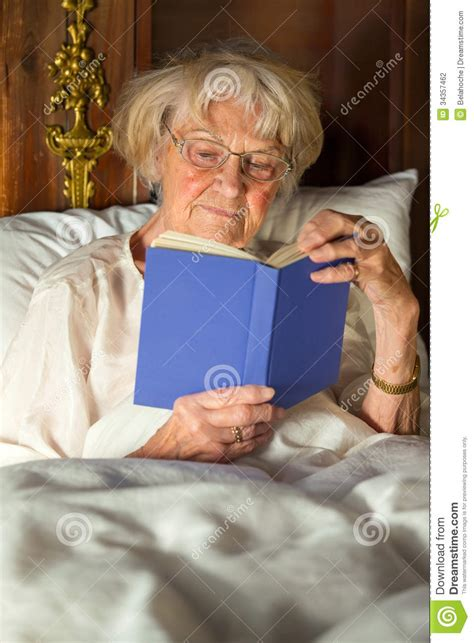 Bed Pillows For Elderly Elderly In Nightgown Reading In Bed Stock