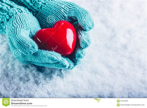 woman hands in light teal knitted mittens are holding a