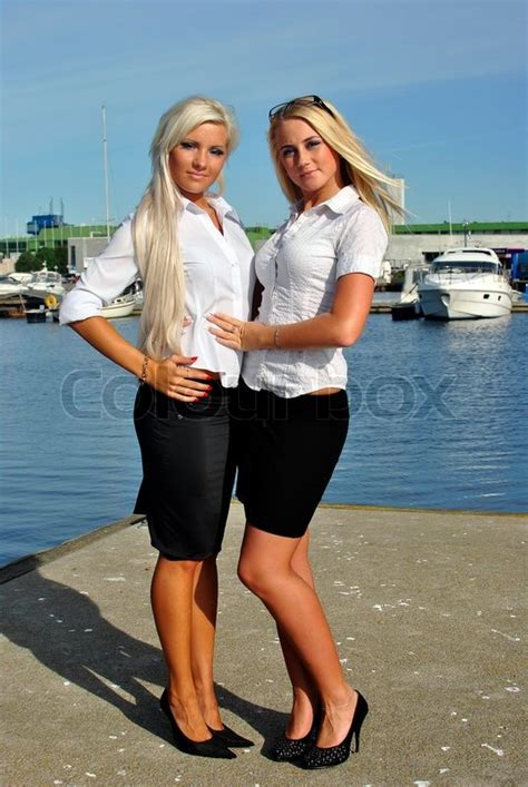 girls on boats two girls blonde stand on the pier boats on the background