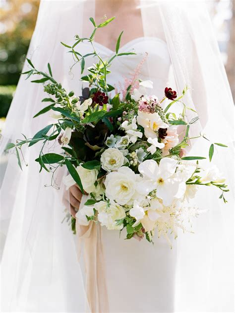 bridal bouquet of garden roses anemones nandina and greenery brides