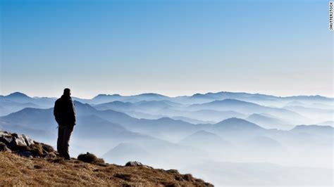 man standing on mountain top thinking business cnn com