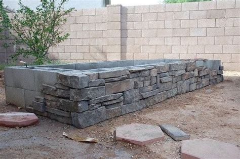 stone veneer over concrete block bed could work for a